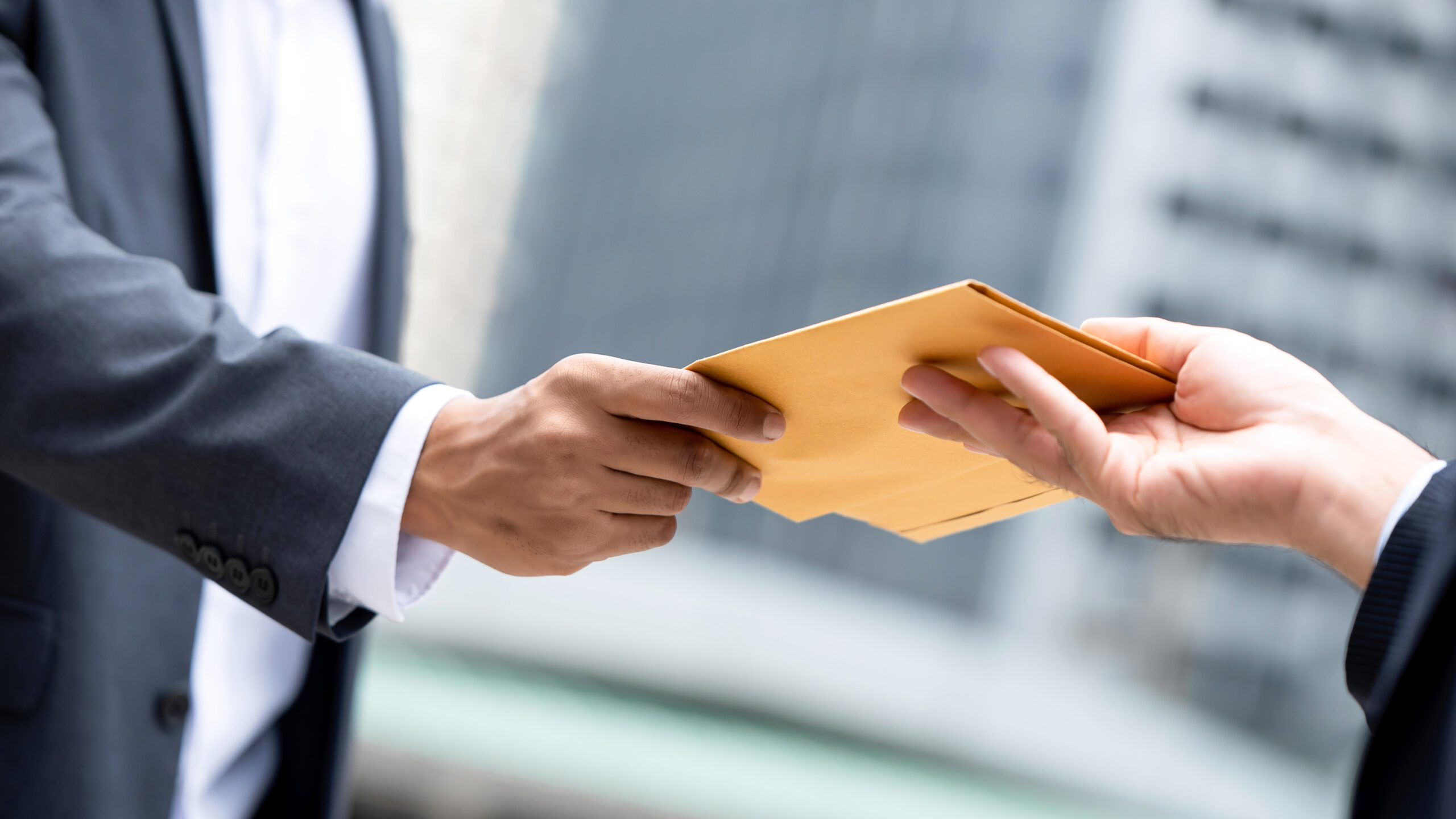 Close up portrait of  businessman hand recieving yellow envelope from boss in urban city background