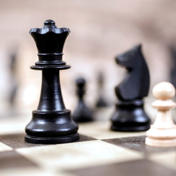 Chess game.  Various chess pieces form a strategic move on a beige and black chess board.  A black king is focal point.  No people.  Strategy concept.